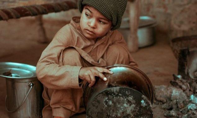 Un enfant tenant une marmite, Pakistan.